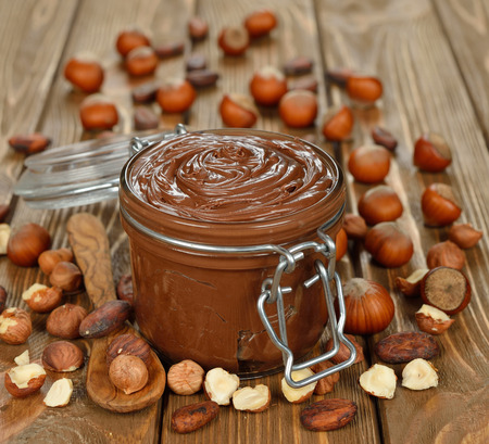 hazelnuts: Chocolate paste in a glass jar on a brown background