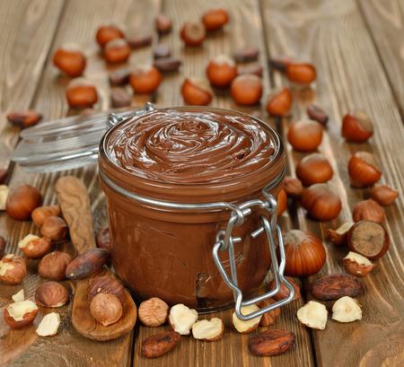 cacao: Pasta de chocolate en un frasco de vidrio sobre un fondo marrón
