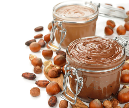 Chocolate paste in a glass jar on a white background photo