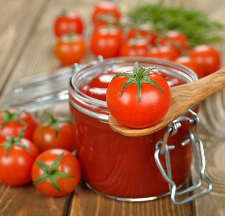 Tomato sauce in a glass jar on a brown table