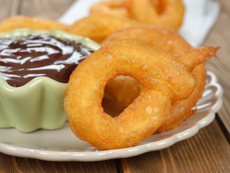 Spanish churros with chocolate on brown background closeup photo