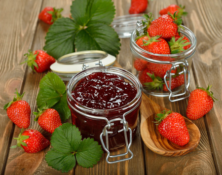 preserving: strawberry jam on a brown background