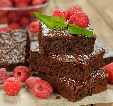 Chocolate brownies with raspberries on brown background Reklamní fotografie