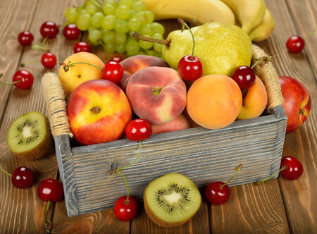 wooden box: Various fruit in a wooden box on brown background