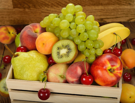 Various fruit in a wooden box on brown background