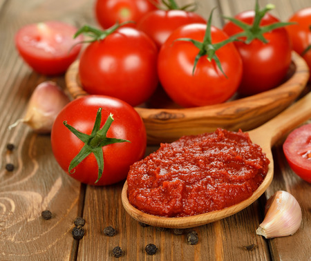 tomato paste in wooden spoon on brown background Stock Photo