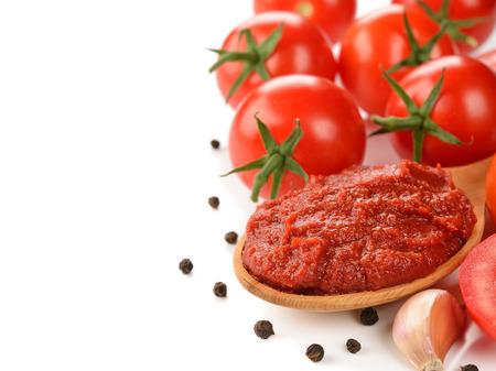 tomato paste: tomato paste in wooden spoon on  white background