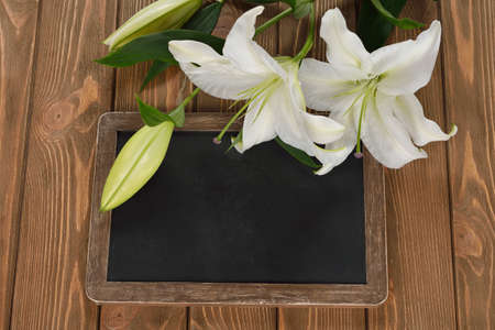writing board: Writing board and a white lily on a brown background Stock Photo