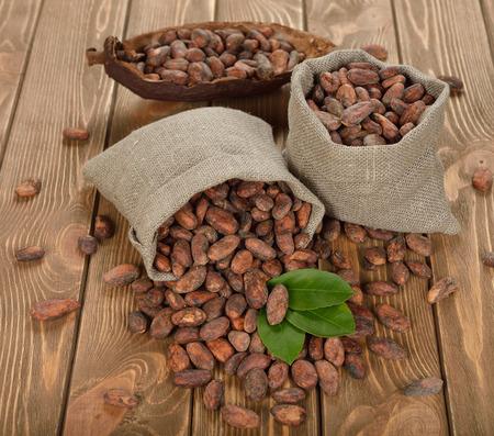 cacao beans: Granos de cacao en una bolsa en un fondo marr�n Foto de archivo