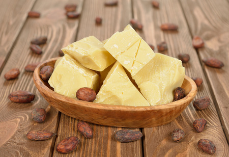 Natural cocoa butter in a wooden bowl on a brown background Stock Photo