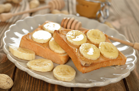 banana bread: Toast with peanut butter and banana on a brown table