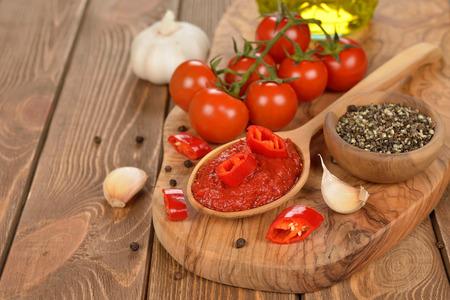tomato paste: Tomato paste in wooden spoon on brown background