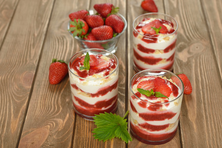 Dessert with strawberries and whipped cream on a brown background