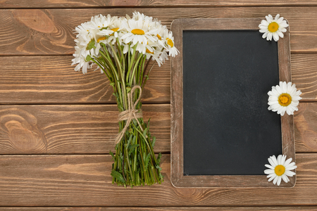 writing board: Writing board and daisies on a brown background, top view