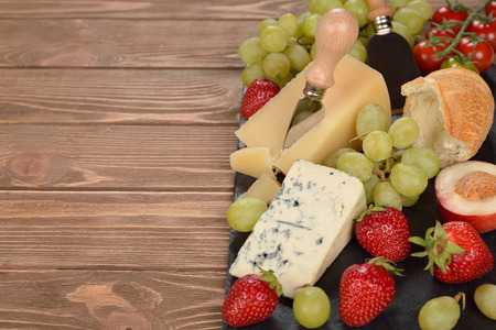 roquefort: Cheese, grapes and fruit on a brown background