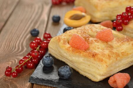 puff pastry: Puff pastry with fruit on a brown background