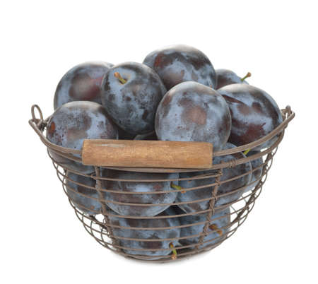 prunes: Fresh prunes in a basket on a white background Stock Photo