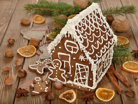 Christmas gingerbread house decorated with icing on a brown background