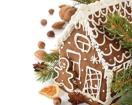 Gingerbread house decorated with icing on a white background