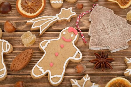 man nuts: Gingerbread man, nuts and spices on a brown background