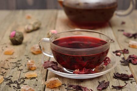 Hibiscus tea in a glass cup on a wooden background