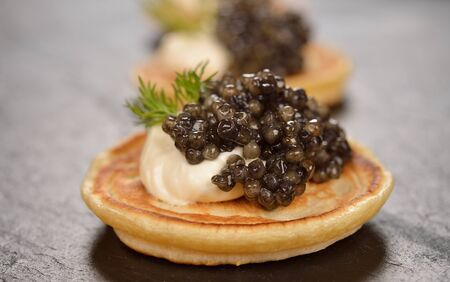 Mini pancakes with black caviar on a black background