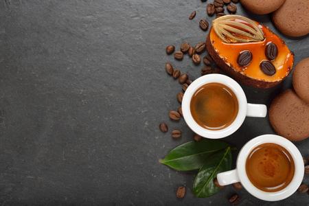 taza: espresso fresco y pastel sobre un fondo negro