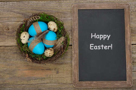 nest egg: Eggs in a nest on a wooden background, Easter concept