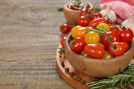 Various cherry tomatoes on a wooden background