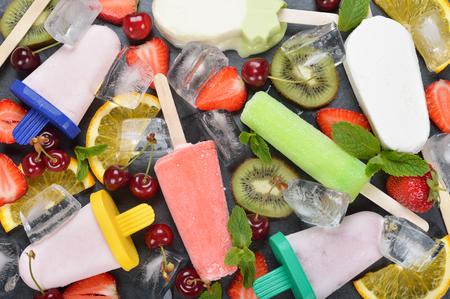 paletas de hielo: Ice cream, popsicles, ice and various fruits on a black plate Foto de archivo
