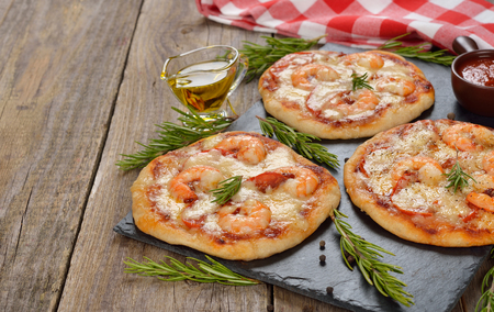mini pizza: Mini pizza with shrimp and rosemary on a wooden background Stock Photo