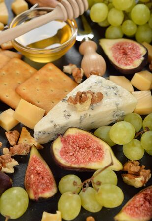Blue cheese with grapes, figs and honey on black background