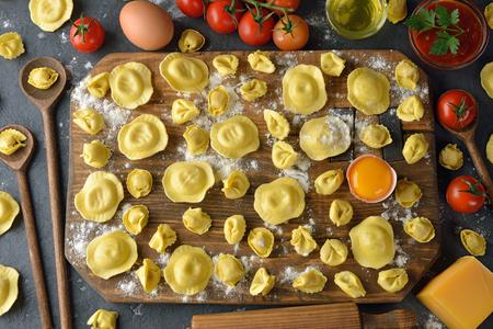 Raw tortellini and ravioli on a gray background