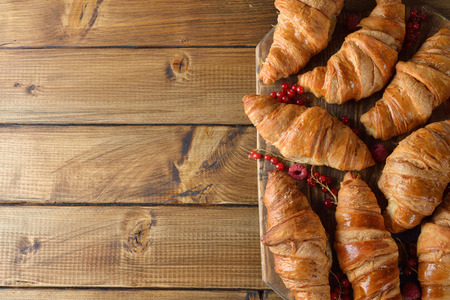 Croissants with berries on a wooden background