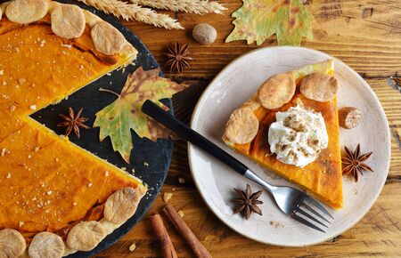 Pumpkin pie decorated with whipped cream on a brown background 写真素材