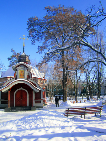 Orthodox church on the white snow background with alone man and bench in park. Christmas background. Happy new year.