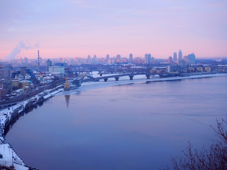 Purple sunset time over most city. Panorama of Kiev with river Dnieper. True city, sunrise and sunset today.