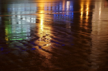 Colorful water reflection on the road. City lights reflected in puddle. Rain weather, puddle of infinity, rain night