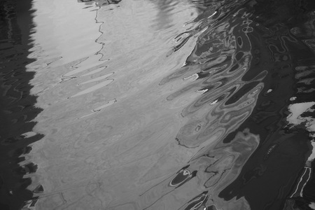 Flooded house. Reflection home with windows and trees in puddle. Raining autumn sunny weather. Black and white photo. Rain today. Lines are soft blurred curved wavy. Inverted image
