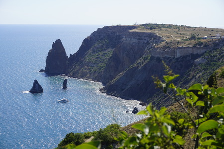 Monastery, Fiolent, Sevastopol, Crimea. Sharp rock-sail with boats in Black sea with green bushes on foreground. Natural colors photography.