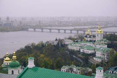 Domes of the Kiev-Pechersk Lavra in foggy rainy weather. The monastery. Ancient shrine. Raining autumn day, vintage color, autumn forry weather. Cold colors.