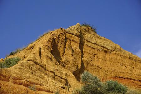 Bright sandy yellow orange red dune (rock, hill) under blue sky with white grey clouds Reklamní fotografie