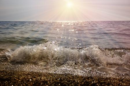 Lubimovka, Sevastopol, Crimea, Russia. Sunny shore line beach with Black sea and  bright sun with long rays. Travel concept.