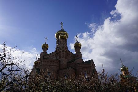 ホロシエフスカヤ・プスティン、キエフ(キエフ)、ウクライナ。オレンジレンガの修道院(修道院、教会、寺院)、十字架と金色のドーム
