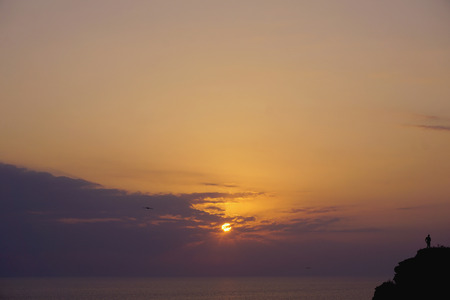 Silhouette alone (lonely) man are standing on hill against sunset purple lilac yellow orange sky with round sun over sea