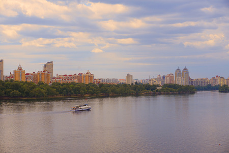 Yacht (ship, boat) goes on surface of Dnieper (Dnipro, Dnepr) river against background of city skyscrapers with yellow blue sky Reklamní fotografie