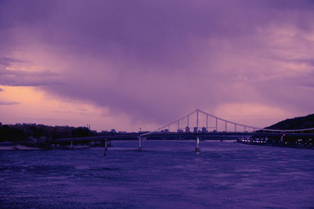 Bridge reflection in water surface of river Dnieper duaring sunset time. Toned image: purple, violet, yellow, orange colors.
