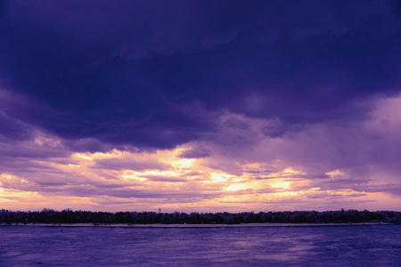 Landscape reflection in water surface of river Dnieper duaring sunset time. Toned image: purple, violet, yellow, orange colors.