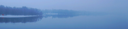 Panoramic view to foggy sunset time on river Dnieper, Kiev. Kyiv, Ukraine. Forest reflection in water Reklamní fotografie