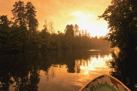 Forest reflection with boat on lake or river. Golden hour, orange sunset time. Reklamní fotografie